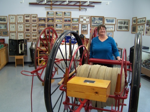 Cathy MacKenzie stands in the section of the fire department museum housing old hose wagons.