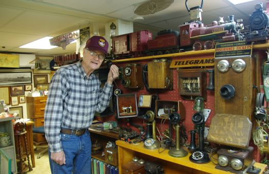 Tony Kalkman checks some of the old railway telephones that are in his collection. On the shelf above is a miniature steam locomotive and miniature cars, duplicates of the railway stock that once ran up and down local rails. The miniatures were made from scrap material. (E. Coleman).